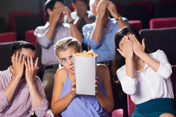 Terrified friends watching horror movie in cinema
