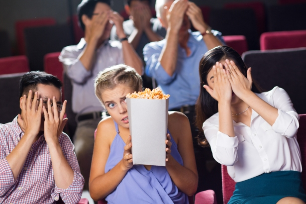 Terrified friends watching horror movie in cinema