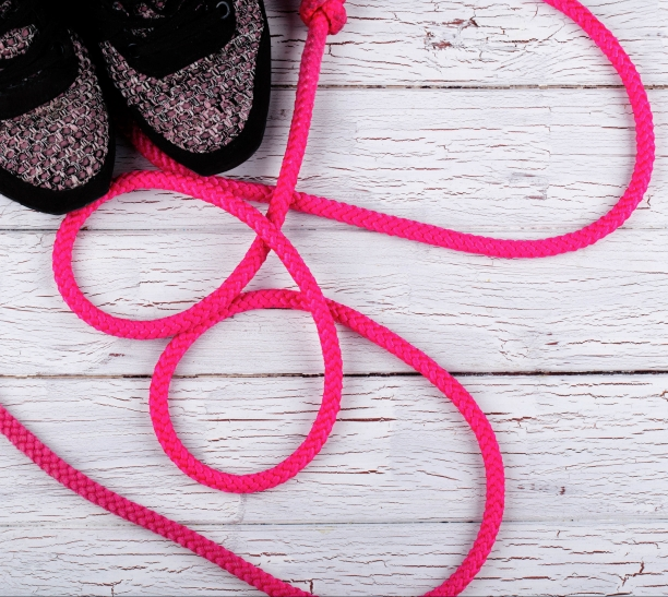 Pink jump rope lies by black snickers on white floor