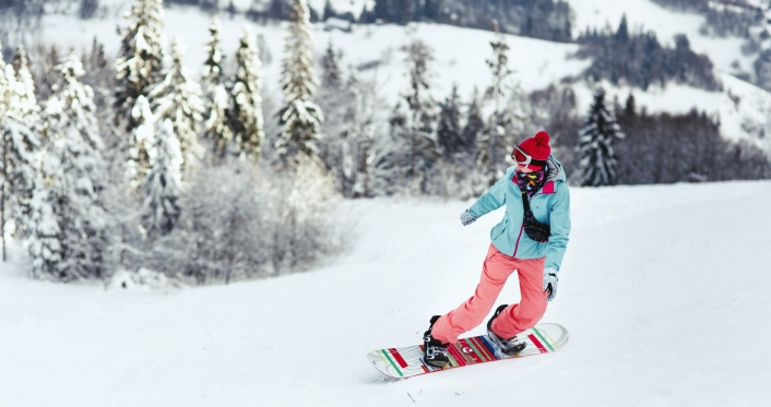 Woman in ski suit looks over her shoulder going down the hill on
